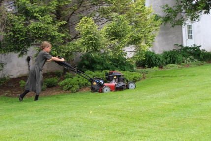 Amish girl mowing lawn